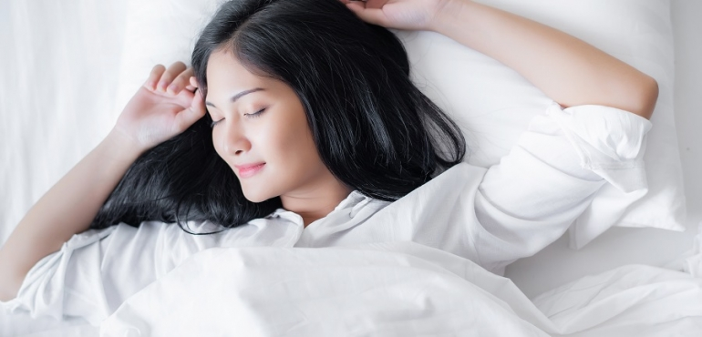 Beautiful young pretty Asian woman wake up and make happy smile with white shirt at the white bed in the morning.
